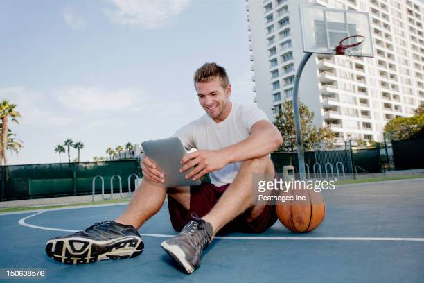 Caucasian man using digital tablet on basketball court
