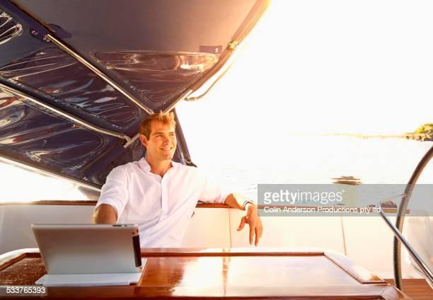 Caucasian man using digital tablet on yacht