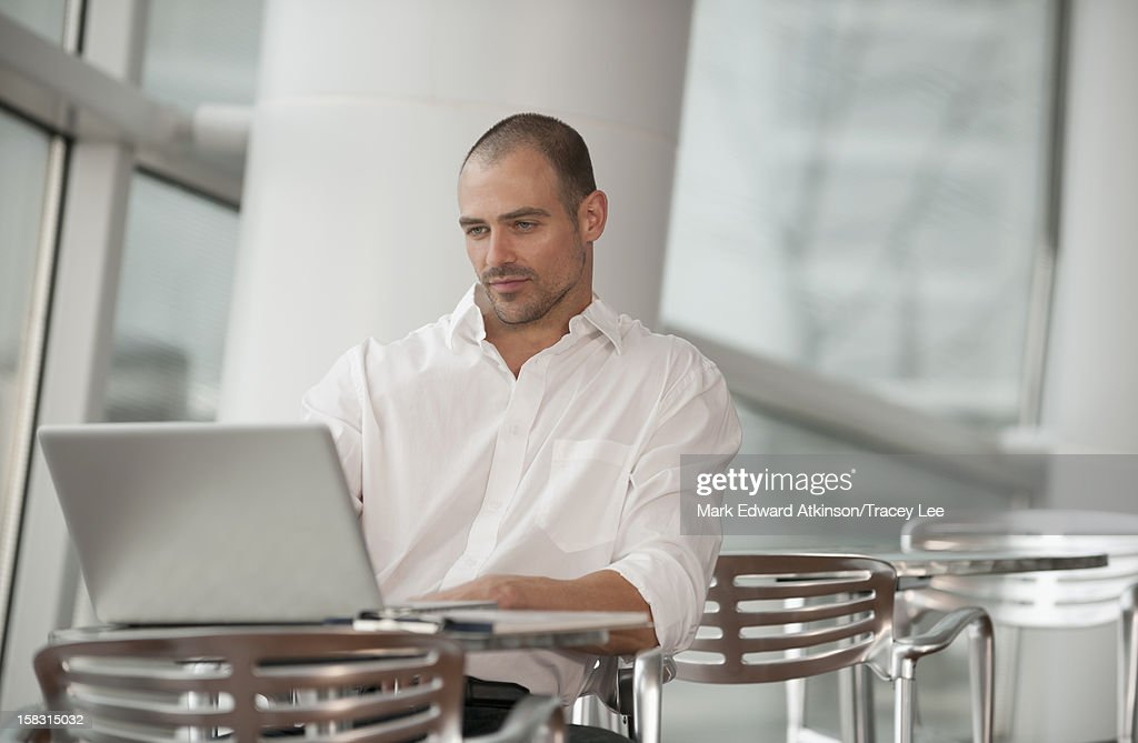 Caucasian man using laptop in cafe : Stock Photo