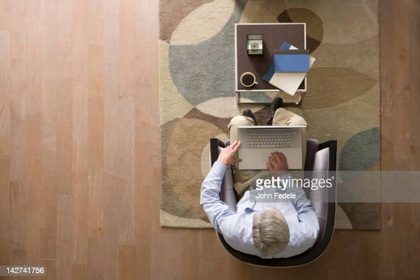 Caucasian man using laptop in living room
