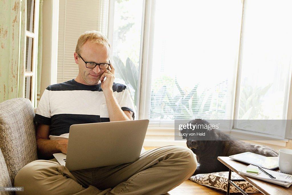 Caucasian man using laptop on sofa