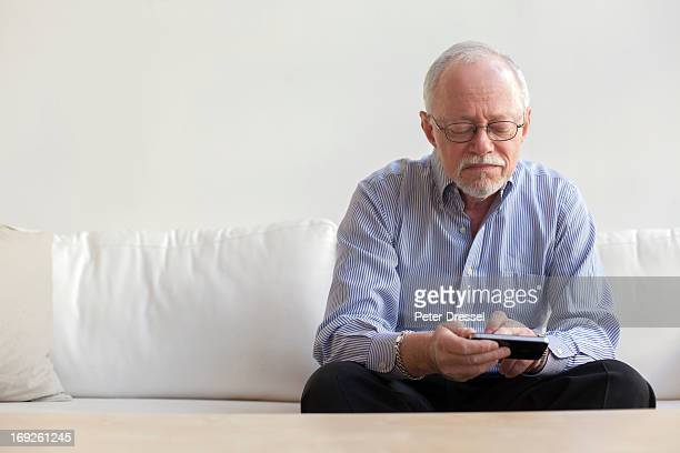 Caucasian man using tablet computer on sofa