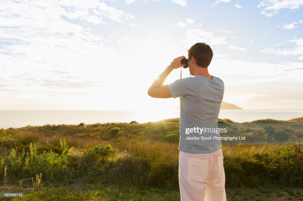 Caucasian man viewing seascape with binoculars