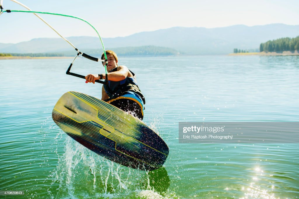 Caucasian man wakeboarding on lake