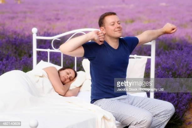 Caucasian man waking in bed in lavender field
