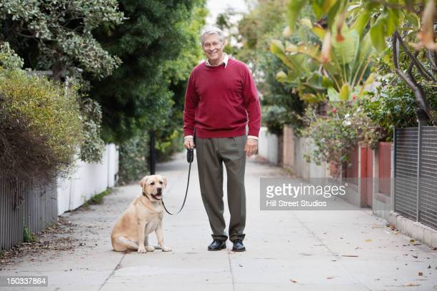 Caucasian man walking dog in alley