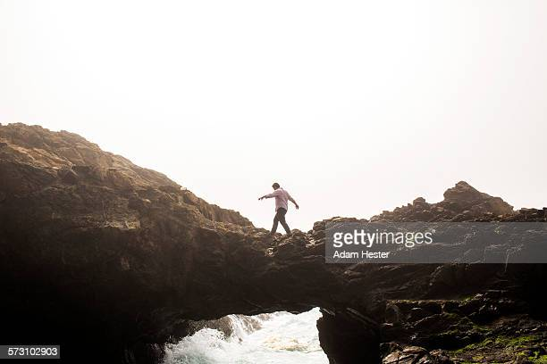 Caucasian man walking on bridge over ocean waves