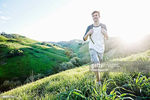 Caucasian man walking on rural hillside