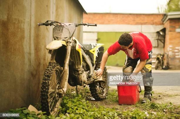 Caucasian man washing dirt bike