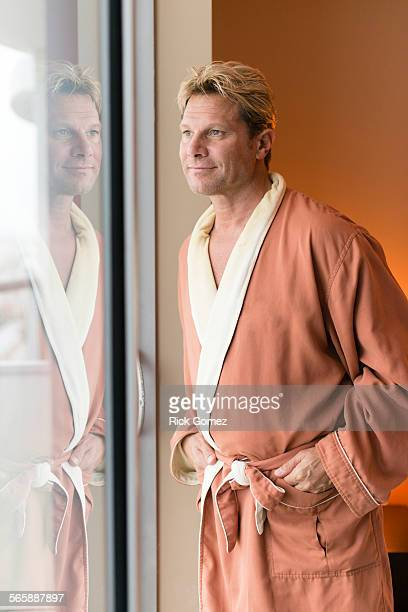 Caucasian man wearing bathrobe at bedroom window