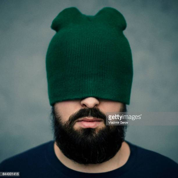 Caucasian man wearing beanie hat over eyes