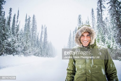 Caucasian man wearing fur parka hood in snow