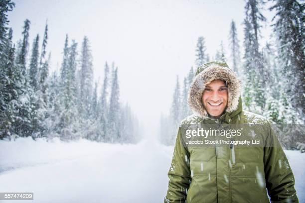 Caucasian man wearing fur parka hood in snow