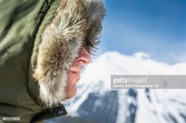 Caucasian man wearing fur parka hood near mountain