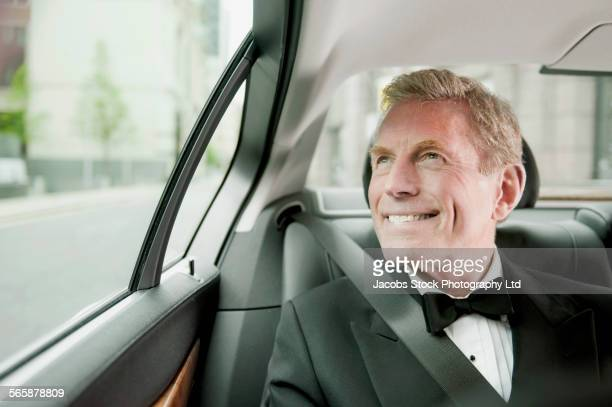 Caucasian man wearing tuxedo in back seat of car