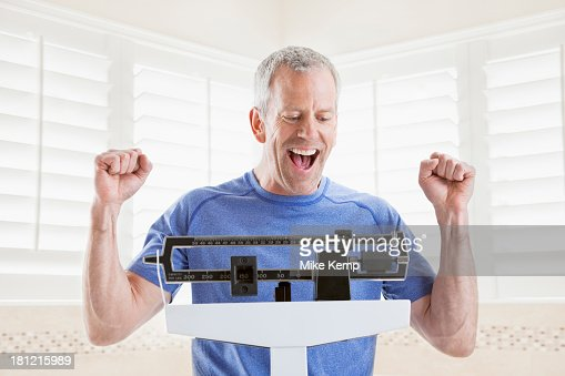 Caucasian man weighing himself : Stock Photo