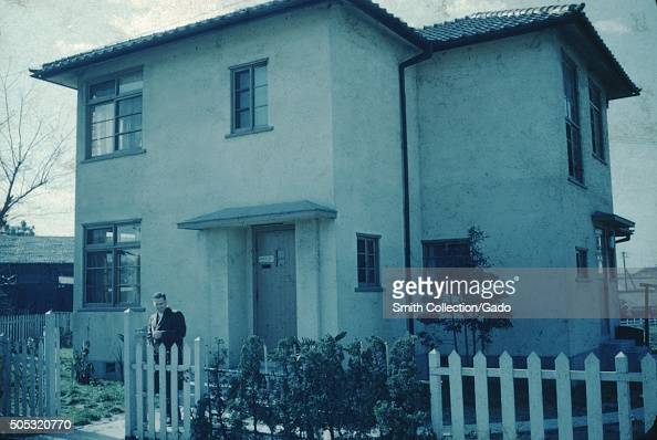 Caucasian man with a camera standing outside a plain white stucco home in a Christian missionary complex Japan 1951