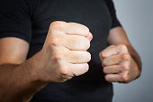 Caucasian man with a threatening gesture, ready to punch or fight with his fists