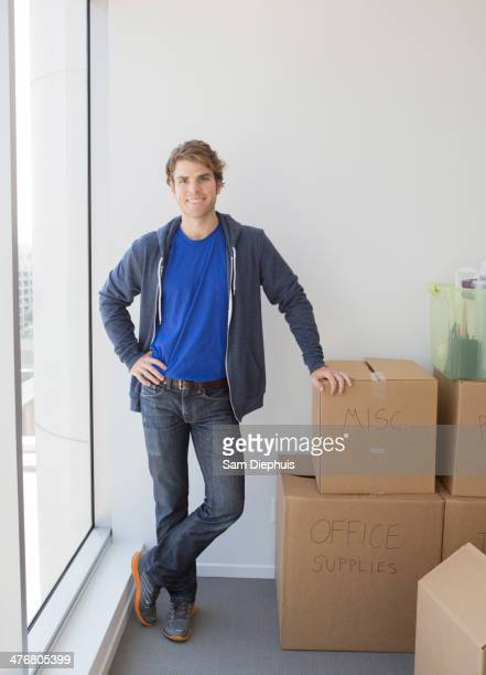 Caucasian man with cardboard boxes in new home