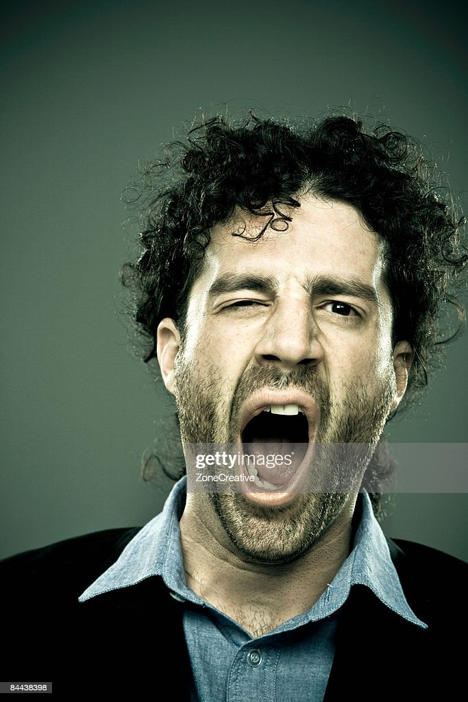 Caucasian man with curly hair yawn portrait