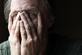 Middle aged man looking through his fingers into the camera; a glimpse of sadness in his eyes.  Related images:  [url=file_closeup.php?id=604679][img]file_thumbview_approve.php?size=1&id=604679[/img][