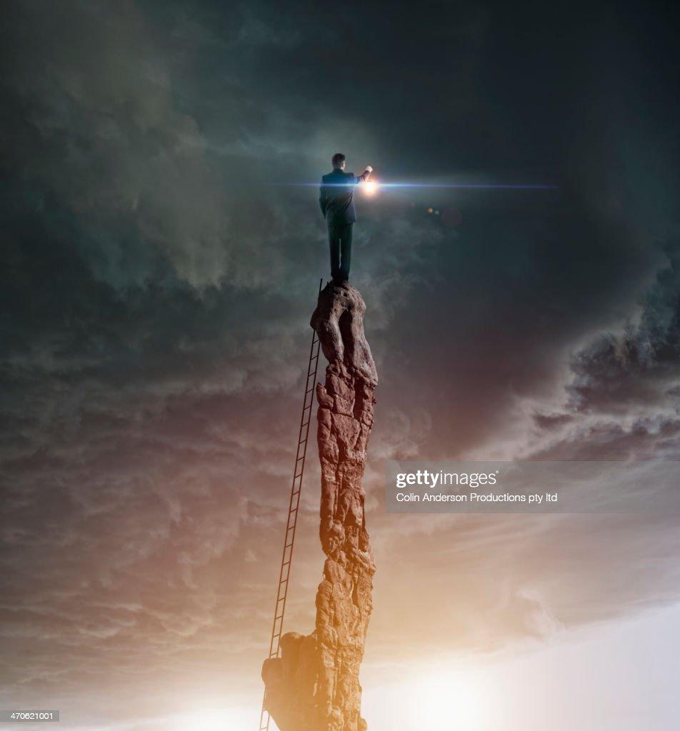 Caucasian man with lantern on rocky pillar