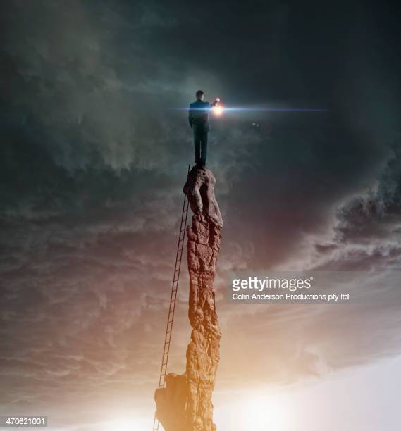 Caucasian man with lantern on rocky pillar