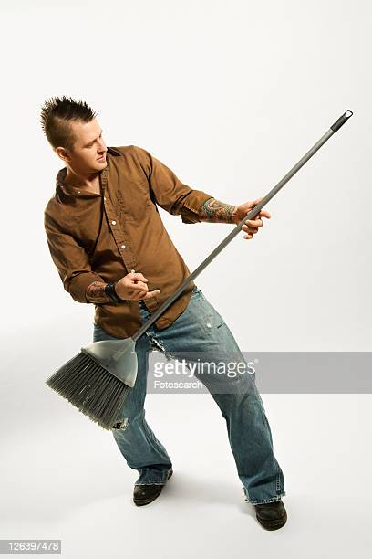 Caucasian man with mohawk playing broom like guitar against white background.