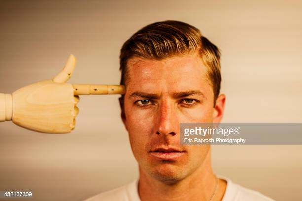 Caucasian man with wooden finger pointed at head