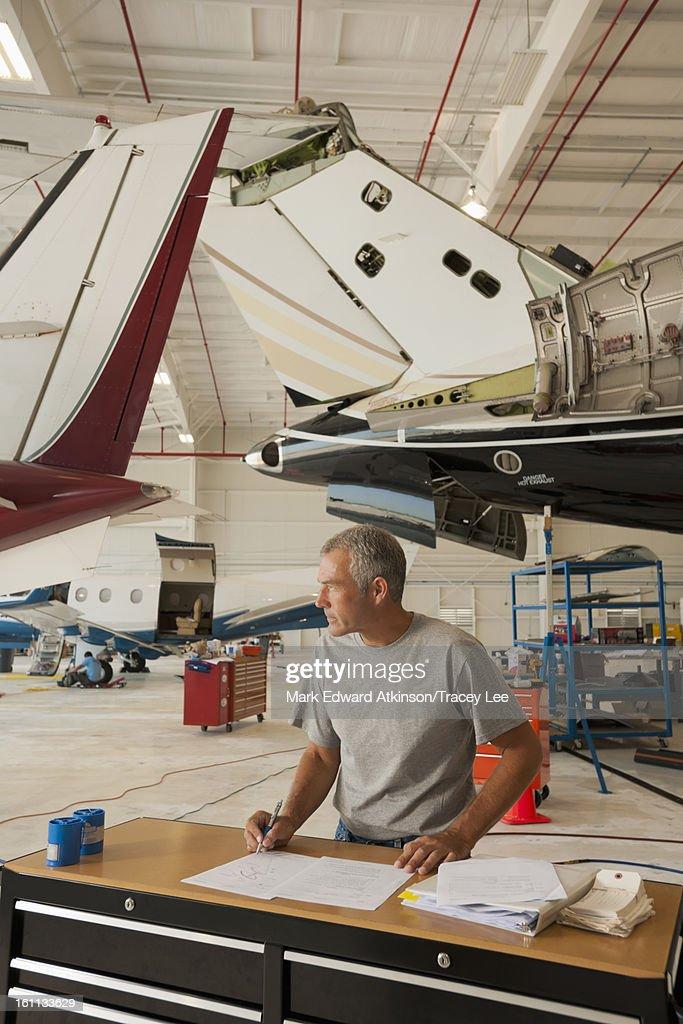 Caucasian man working in airplane hangar
