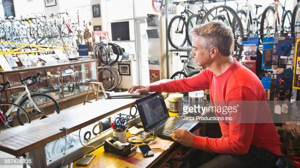 Caucasian man working on laptop in bicycle shop