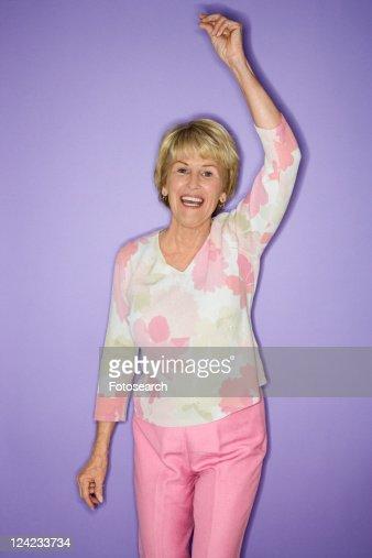 Caucasian mature adult female dancing and smiling.