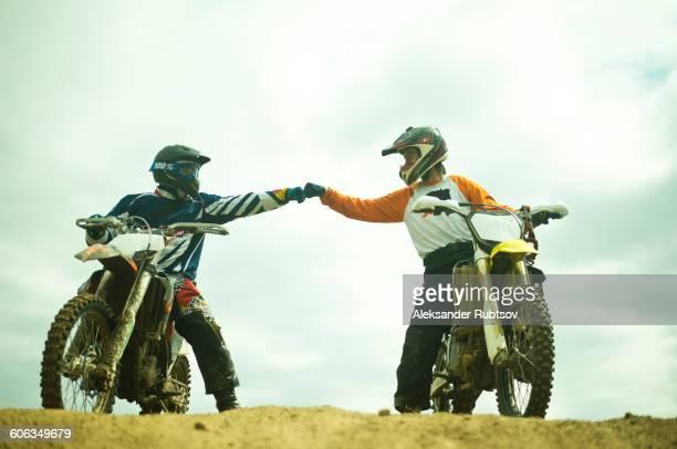 Caucasian men bumping fists on dirt bikes
