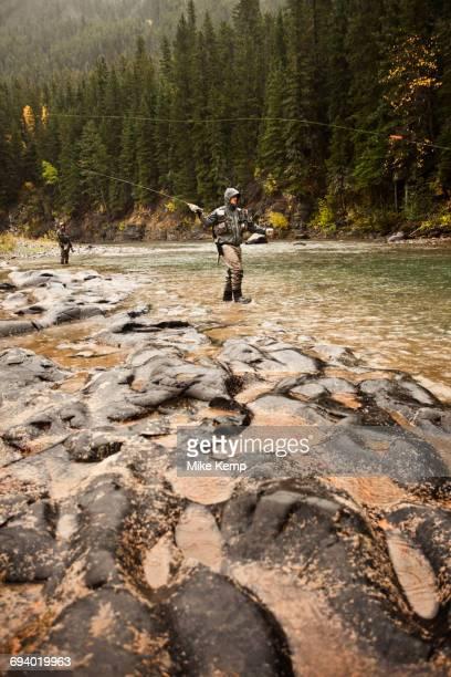 Caucasian men fishing in river