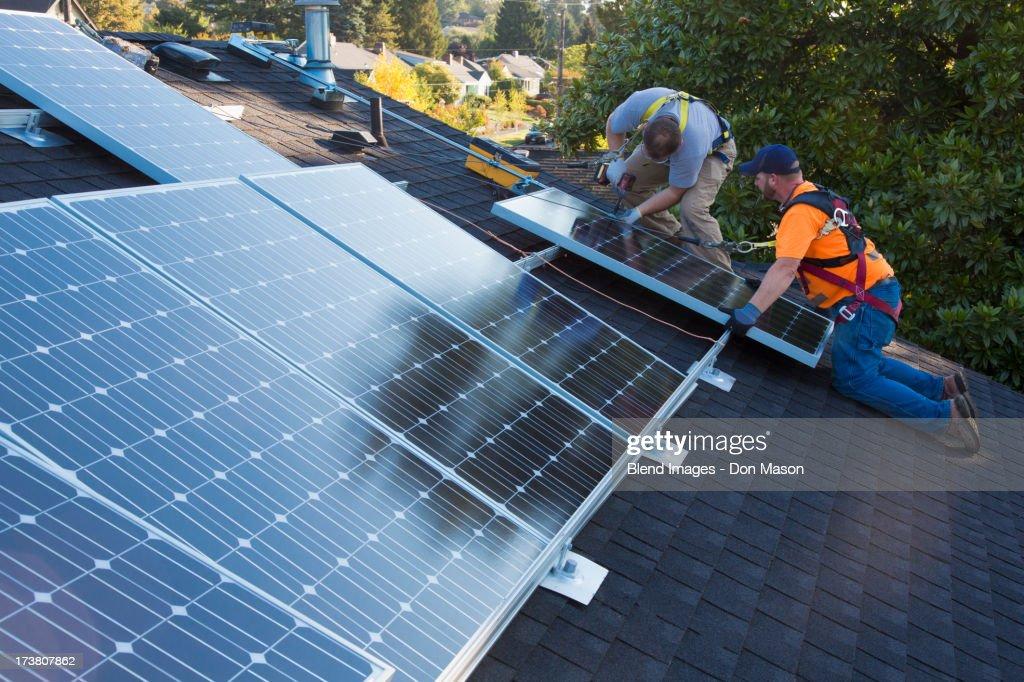 Caucasian men installing panels on roof