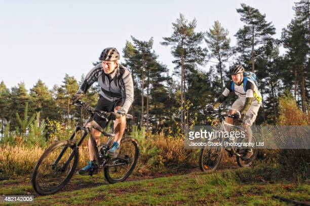 Caucasian men mountain biking on trail