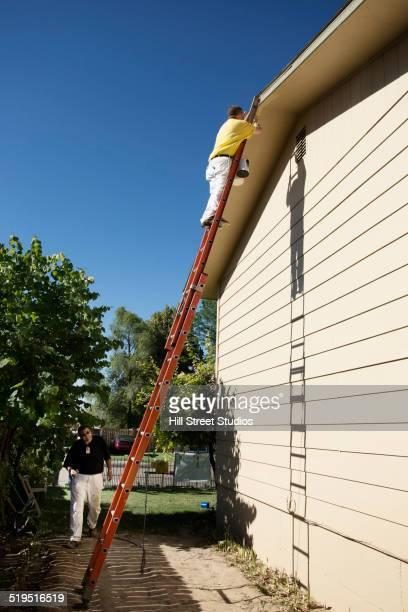 Caucasian men painting house