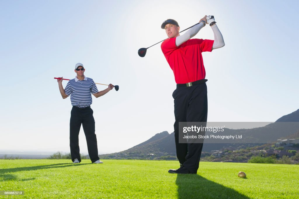 Caucasian men playing golf on course : Stock Photo