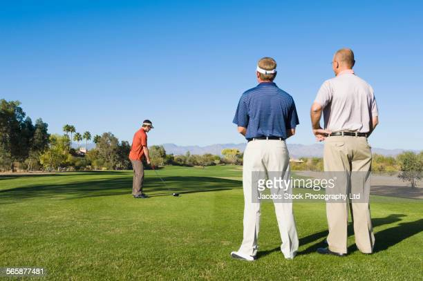 Caucasian men playing golf on golf course