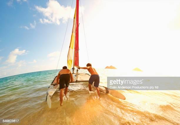 Caucasian men pushing sailboat into ocean from beach