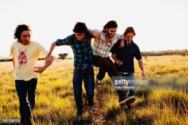 Caucasian men walking together in tall grass