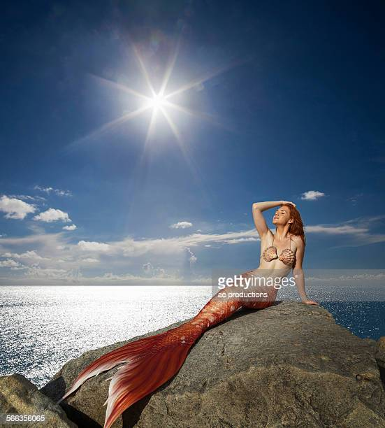 Caucasian mermaid laying on rock near ocean