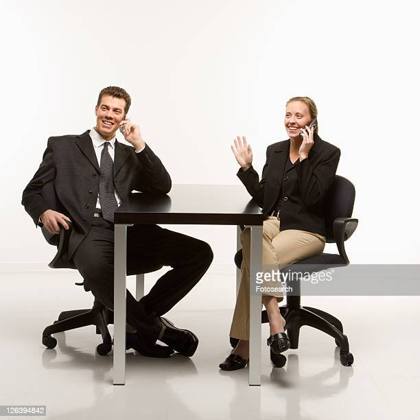 Caucasian mid-adult businessman and woman smiling while sitting and talking on cell phones.