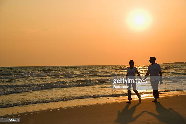 Caucasian mid-adult couple holding hands and walking down beach at sunset.