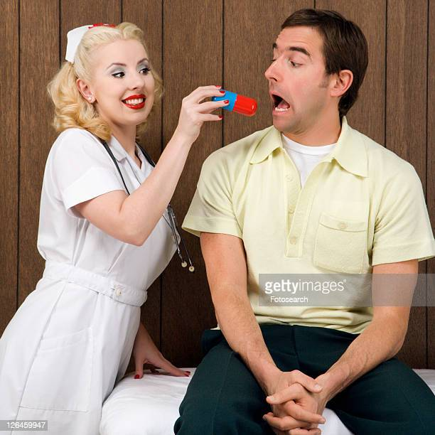 Caucasian mid-adult female nurse giving mid-adult man giant pill.