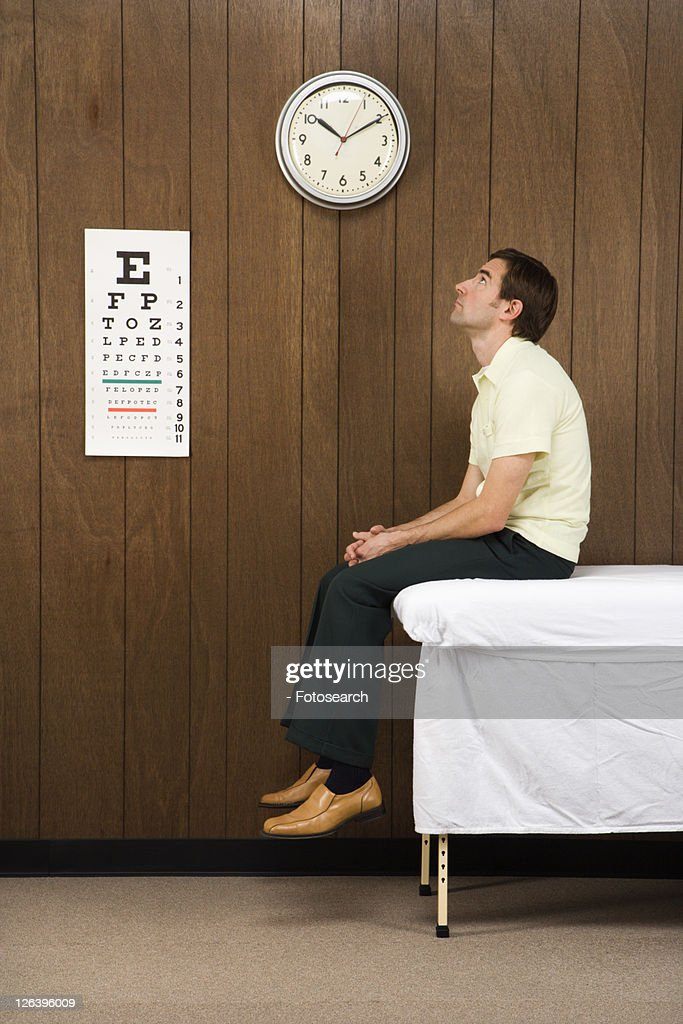 Caucasian mid-adult male waiting on table in retro doctor's office. : Stock Photo