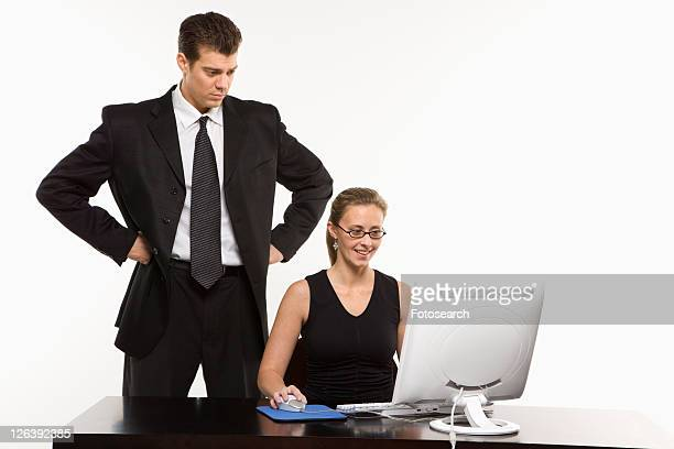 Caucasian mid-adult man with hands on hips looking over shoulder of woman sitting at computer.
