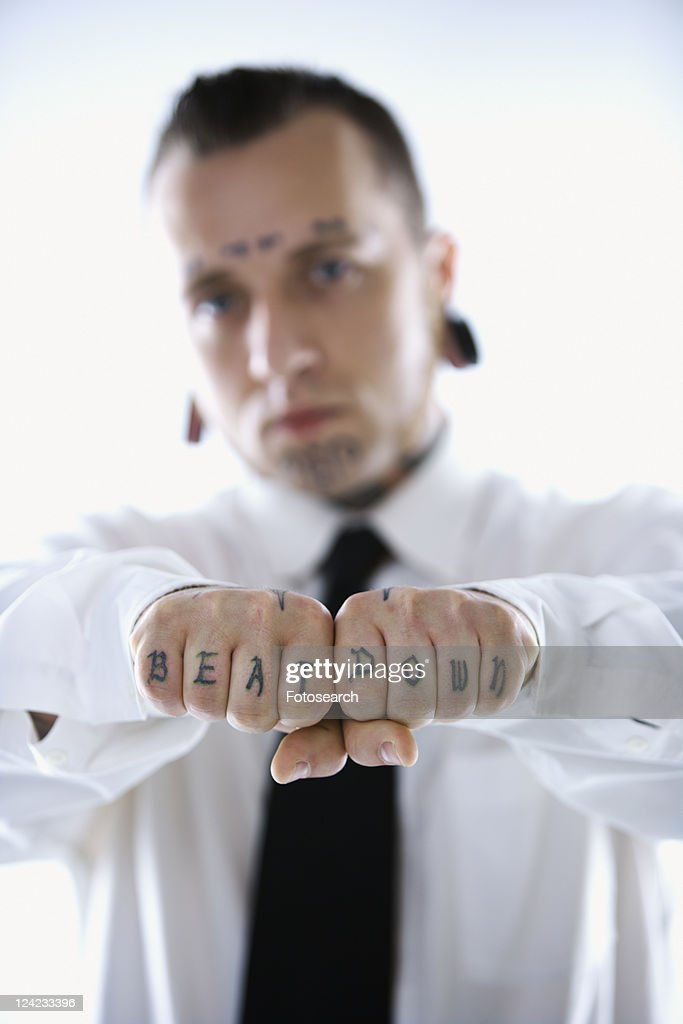 Caucasian mid-adult man with tattoos and piercings holding out fists reading beat down.