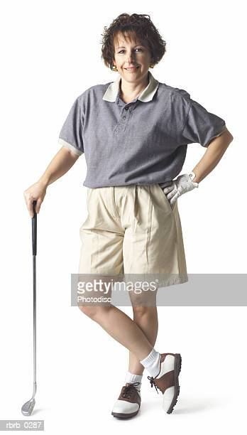 caucasian middle aged brown haired woman wears gray tan stands hand on hip leans on club and smiles