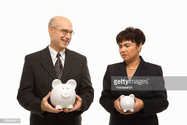 Caucasian middle-aged businessman and Filipino businesswoman holding different sized piggybanks.